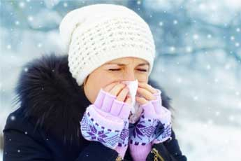 Una ragazza che si soffia il naso a causa di un'allergia invernale